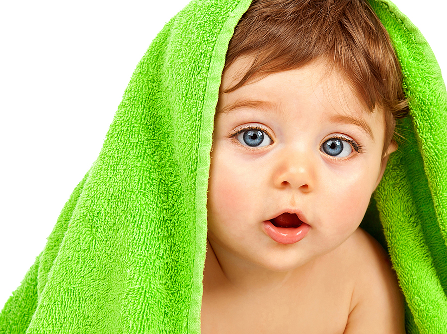 Image of cute baby boy covered with green towel isolated on whit
